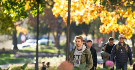 Student with Pitt sweatshirt walking among fall foliage