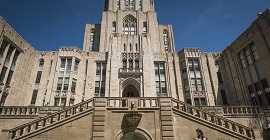 Student walking in front of the base of the Cathedral of Learning