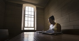 Student studying by window in the Cathedral of Learning