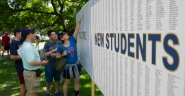 Students and parent looking at welcome sign for new students