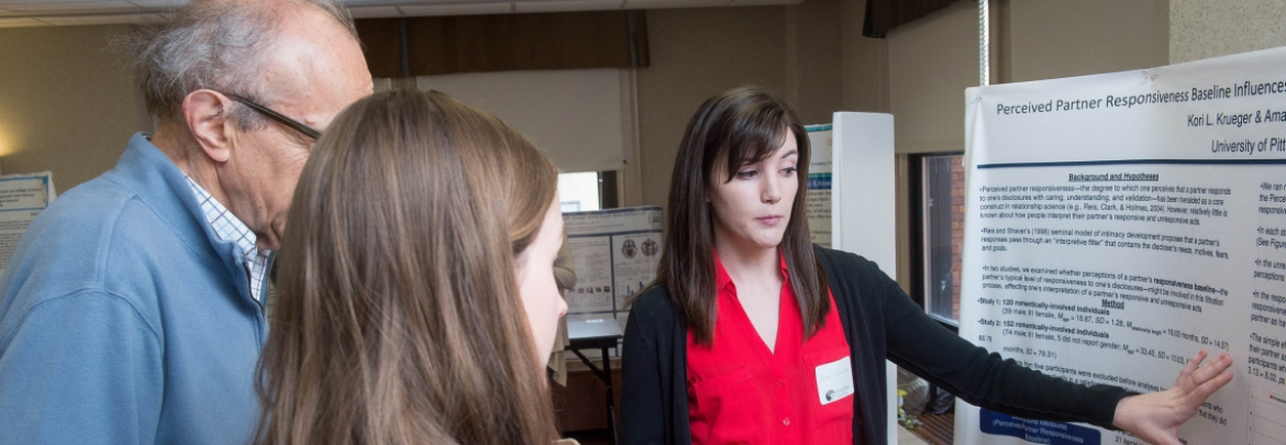 Student explaining her reserch with a poster presentation to two viewers